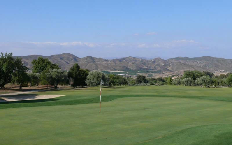 mountains form a backdrop to one of lauro's greens